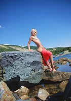 Skinny sexy blonde teen posing naked on the rocks