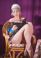 Brave goddess blonde is reading her favorite book on the chair indoors